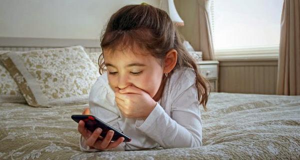 Bocah perempuan yang asyik main gadget dan berpengaruh pada semangat belajarnya